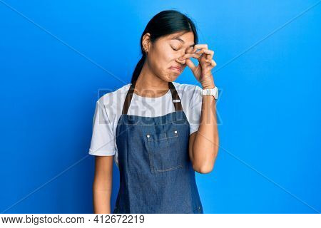 Young chinese woman wearing waiter apron smelling something stinky and disgusting, intolerable smell, holding breath with fingers on nose. bad smell