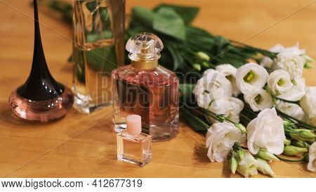 Small Bottles With Perfume And Flowers On A Wooden Table. Concept. Close Up Of Woman Choosing A Frag