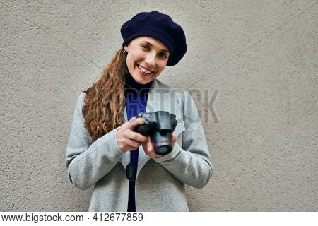 Young blonde woman smiling happy using reflex camera at the city.