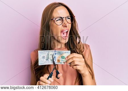 Young brunette woman cutting dollars with scissors for currency devaluation angry and mad screaming frustrated and furious, shouting with anger. rage and aggressive concept.
