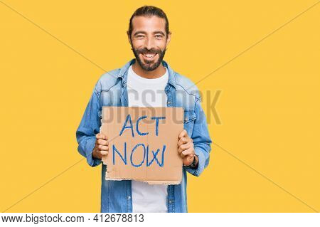 Attractive man with long hair and beard holding act now banner looking positive and happy standing and smiling with a confident smile showing teeth