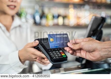 Close Up Shot Of Customer Hand Using Dummy Credit Card For Payment To Waitress At Cashier In Cafe Re