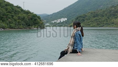 Woman sit on jetty pier and enjoy the scenery view