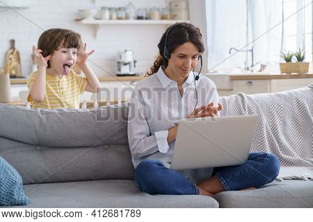 Mother Freelancer Talking On Video Call, Remote Working On Laptop From Home Office With Kid During L
