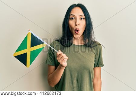 Young hispanic girl holding jamaica flag scared and amazed with open mouth for surprise, disbelief face