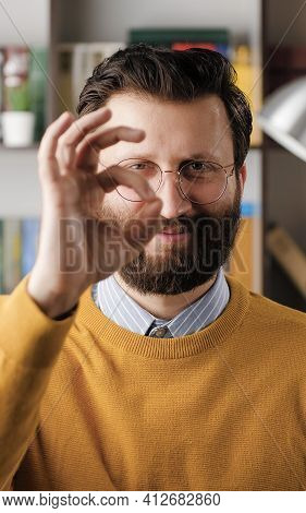 Man Shows Ok. Positive Smiling Bearded Man In Glasses In Office Looks At Camera And Shows Ok Gesture