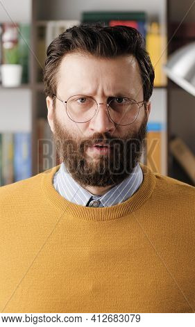 Angry Man, Rage. Angry Annoyed Bearded Man In Glasses In Office Or Apartment Room Looking At Camera.