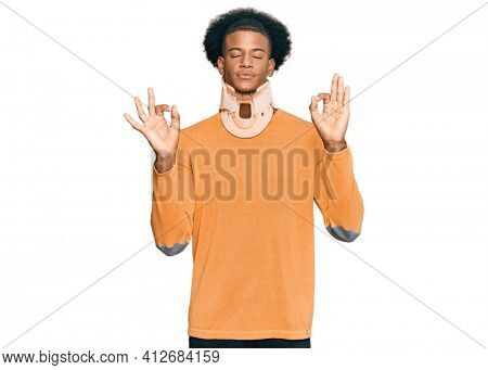 African american man with afro hair wearing cervical neck collar relax and smiling with eyes closed doing meditation gesture with fingers. yoga concept.