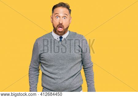 Handsome middle age man wearing business clothes afraid and shocked with surprise and amazed expression, fear and excited face.