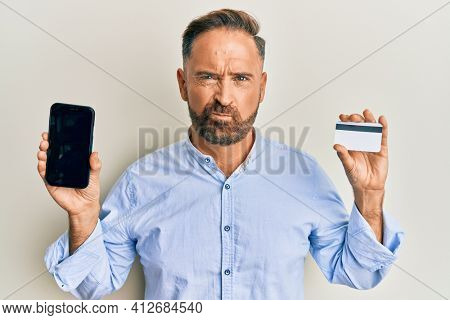 Handsome middle age man holding smartphone and credit card skeptic and nervous, frowning upset because of problem. negative person.