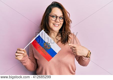 Young caucasian woman holding russia federation flag smiling happy pointing with hand and finger