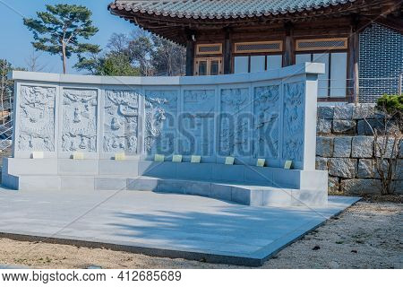 Pyeongteak, South Korea; March 10, 2021: Bas Reliefs Depicting Buddhists Beliefs In Front Of Prayer