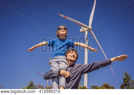 Alternative Energy, Wind Farm And Happy Time With Your Family. Happy Father Carrying His Son On Shou