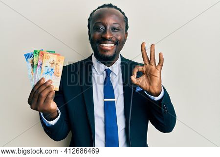 Handsome young black man wearing business suit holding franc swiss banknotes doing ok sign with fingers, smiling friendly gesturing excellent symbol