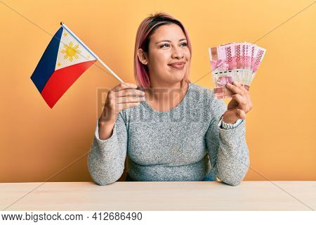 Hispanic woman with pink hair holding philippine flag and philippines pesos banknotes smiling looking to the side and staring away thinking.