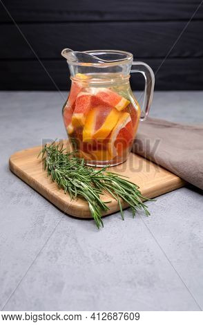 A Transparent Glass Jug With Grapefruit Wedges And Rosemary Are On A Tray On Light Concrete Backgrou