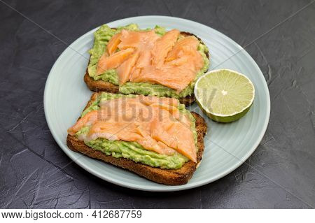 Closeup Of Toast With Dark Rye Bread, Guacamole, Smoked Salmon. Delicious Sandwiches With Avocado An