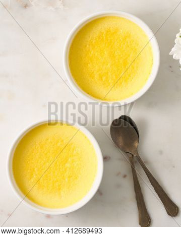 Two Ramekin With Omelet. Backed Eggs In Bowl, Fresh Omelette With Spoon. Top View. Vertical