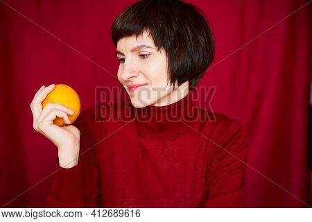 Smiling Mature Brunette Woman Looking At Orange Fruit In Hand, Beautiful Middle-aged Female In Brigh