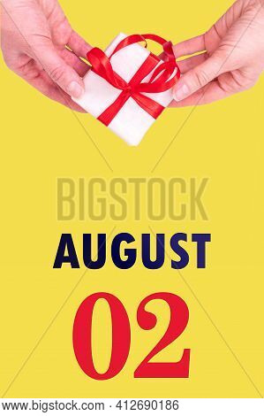 August 2nd. Festive Vertical Calendar With Hands Holding White Gift Box With Red Ribbon And Calendar Date On Illuminating Yellow Background. Spring month, day of the year concept.
