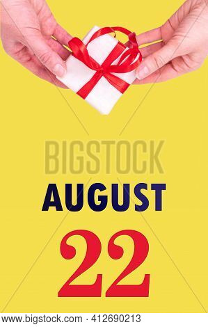 August 22nd. Festive Vertical Calendar With Hands Holding White Gift Box With Red Ribbon And Calendar Date On Illuminating Yellow Background. Spring month, day of the year concept.