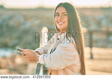 Young hispanic girl smiling happy using smartphone leaning on the balustrade.