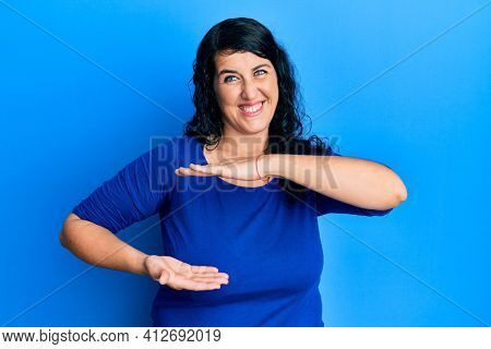 Plus size brunette woman wearing casual blue shirt gesturing with hands showing big and large size sign, measure symbol. smiling looking at the camera. measuring concept.