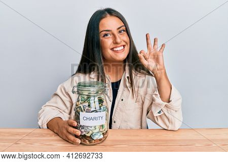 Beautiful hispanic woman holding charity jar with money doing ok sign with fingers, smiling friendly gesturing excellent symbol