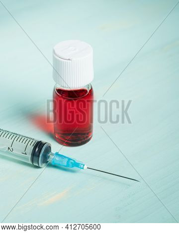 Medical Vaccine Ampule With Red Liquid And Syringe Over Green Table And White Background. Vaccinatio