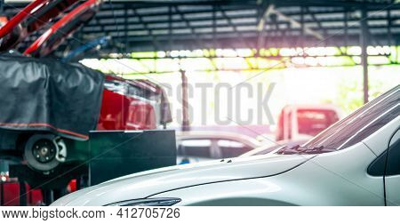 Auto Repair Shop. White Car On Blurred Red Suv Lifted In Garage For Repair And Maintenance Service.