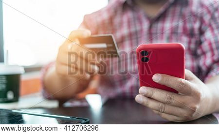 Man's Hands Holding A Credit Card And Using Smart Phone For Online Shopping. Credit Card For Pay And
