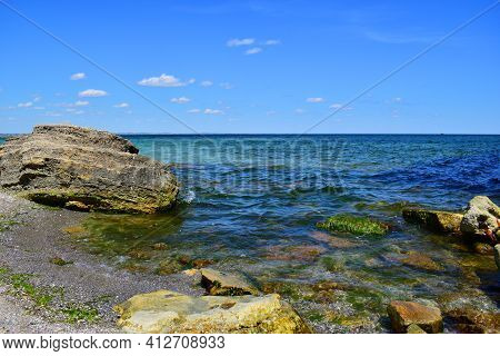 A Picturesque Seascape Overlooking The Blue Sea, Rocks And Stones On A Bright Sunny Day. The Waves B