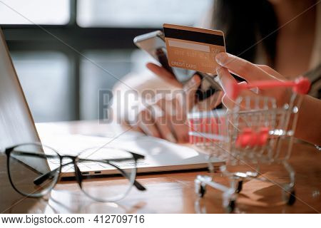 Woman Using Mobile Smart Phone And Mock Up Credit Card Making Online Payment With Her Friend In Coff