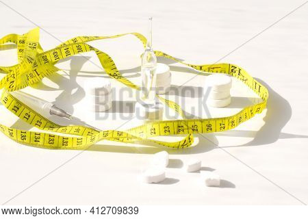 Diet Concept.weight Loss Pills And Yellow Measuring Tape. Slim By Pills, Dangerous For Health.