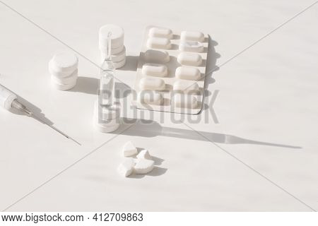 Round Tablets, Ampoule, Syringe On A White Background. A Vaccine Against The Virus.