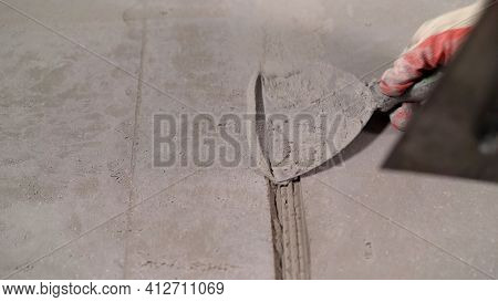 Close-up Of A Hand With A Trowel And Plaster While Repairing A Wall. The Worker Is Filling The Crack