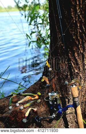 Fishing Silicone Lures Spinning Rod, Old Tree With Textured Bark On The River Bank, Close-up Copy Sp