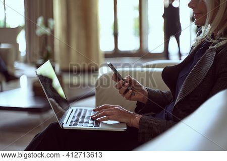 Determined Lady Holding Her Smartphone While Being Seated In A Waiting Area