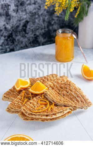 Spring Breakfast. Folded Baked French Crepes Or Russians Blinis In A Round Plate With Orange Slices