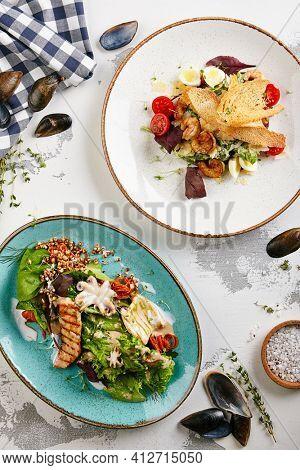 Seafood salad  with shrimp, eggs and crispy bread and mixed greens. Frutti di Mare salad with mixed seafood - salmon, calamari, octopus. Gourmet restaurant salad set top view