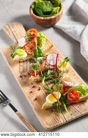 Smoked Salmon Bruschetta with Pita Bread, Quail Egg and Vegetables. Canape fish food appetizer on grey table with wooden board. Healthy, gourmet, appetizers food concept
