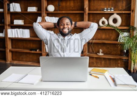 Smiling Afro-american Businessman Holding Hands Behind Head Sitting At Office Desk Behind Laptop. Ha