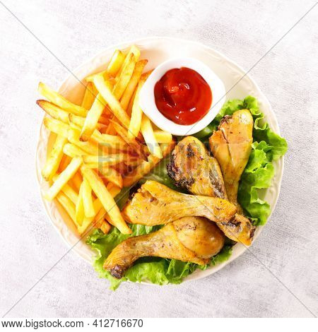 fried chicken leg, french fries and ketchup