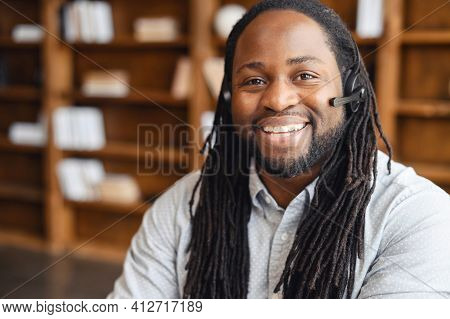 African American Operator With Long Dreadlocks And Headset, Looking At Camera, Working In Callcentre