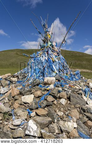 An Religious Ovoo, Buddhism, On The Steppe Of Mongolia With Many Khadags In Summertime.