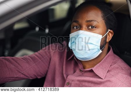Black Ethnic Man Driving, Sitting In The Car Wearing Surgical Face Mask Looking Out The Window Or At