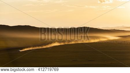 Sunset On The Steppe Of Mongolia With Dust And Moving Car On An Unpaved Road And Mountains In The Ba