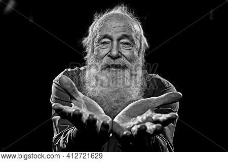 Black-and-white portrait of an old man with a long gray beard stretching out his palms and looking to camera. Studio portrait. Old age.