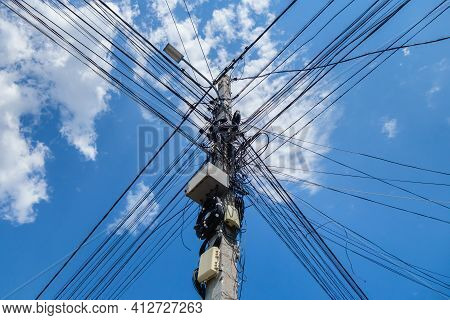City Power Line Pole With A Lantern On Top. Numerous Wires Are Connected To The Post. Pole Is Hung W