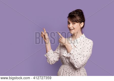 Caucasian Brunette Woman Wearing Dress And Dental Apparatus Is Pointing To The Free Space On A Viole